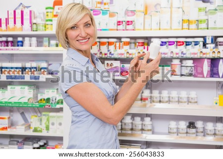 Smiling customer showing a medicine in the pharmacy - stock photo