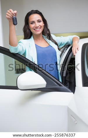 Smiling customer showing her new key at new car showroom - stock photo