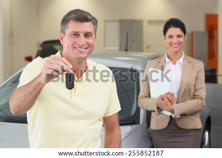 Smiling customer showing his new car key at new car showroom - stock photo