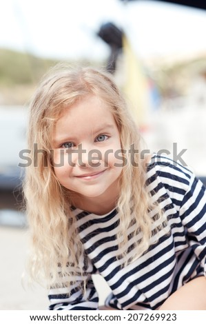 Smiling cute baby girl wearing striped top outdoors - stock photo