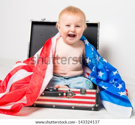 smiling cute baby in a suitcase with American flag - stock photo