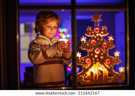 Smiling cute boy standing by window at Christmas time and blowing candle. With colorful lights from Christmas tree on background, selective focus. - stock photo
