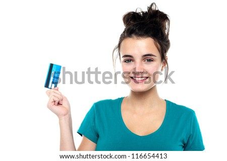 Smiling cute girl posing with her credit card isolated against white background - stock photo