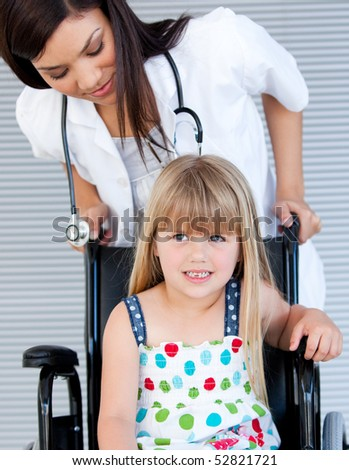 Smiling cute girl sitting on the wheelchair at the hospital - stock photo