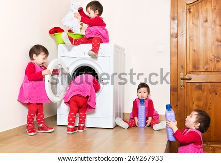 Smiling cute little child using washing machine at home - stock photo