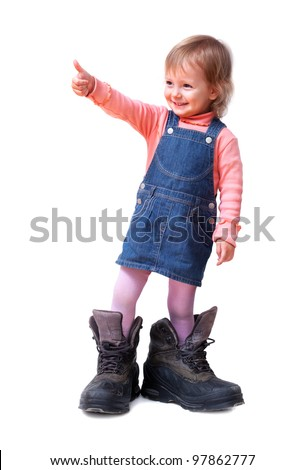Smiling cute little girl in old big tracking shoes shows good-sign, isolated on white - stock photo