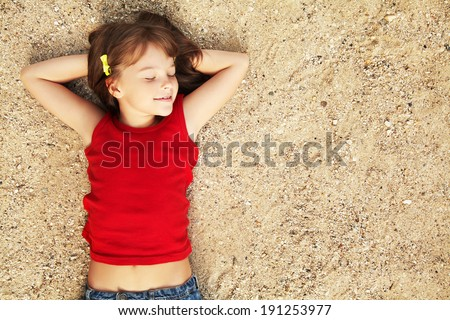 smiling cute little girl lying on the sand. child on vacation - stock photo