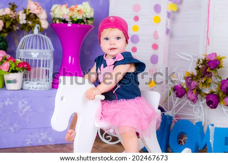 Smiling cute little girl sitting on a horse among flowers  - stock photo