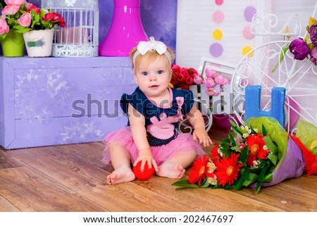 Smiling cute little girl sitting on a house floor among flowers playing  game fun - stock photo