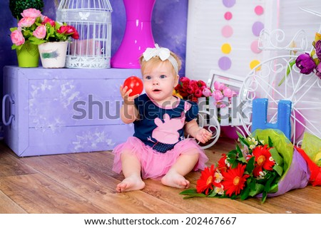 Smiling cute little girl sitting on a house floor among flowers playing with ball game  - stock photo