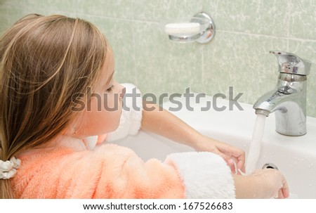 Smiling cute little girl washing hands in bathroom  - stock photo