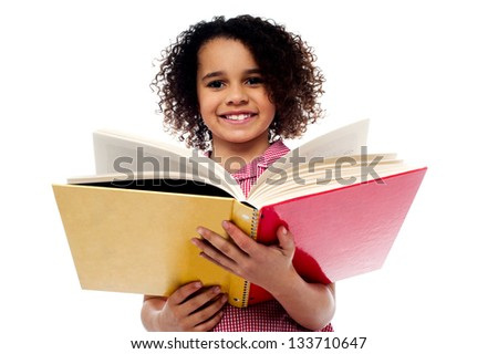 Smiling cute school girl reading a book, preparing for examinations. - stock photo