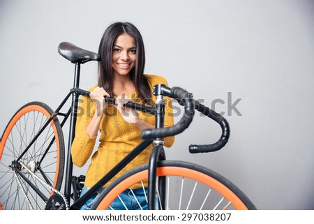 Smiling cute woman holding bicycle on shoulder on gray background. Looking at camera - stock photo