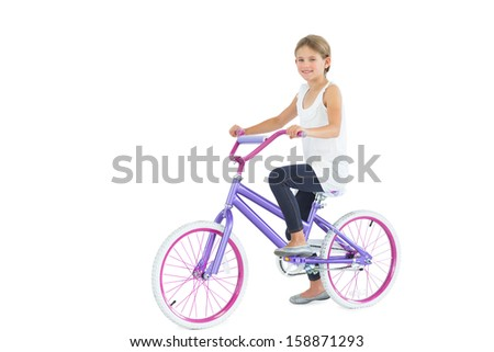 Smiling cute young girl riding bike while posing on white background - stock photo