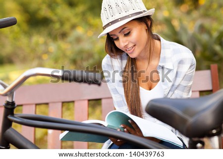 smiling cute young woman studying at the park - stock photo