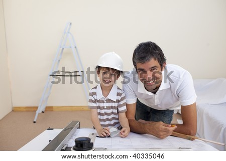 Smiling dad and little boy studying architecture at home - stock photo