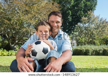 Smiling dad and son with a football in the park on sunny day - stock photo
