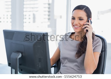Smiling dark haired businesswoman having a phone conversation in her office - stock photo