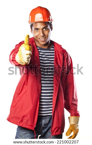 smiling dark-skinned worker with helmet and gloves showing thumbs up - stock photo