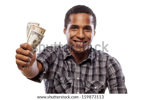 smiling dark-skinned young man shows a wad of cash in hand - stock photo