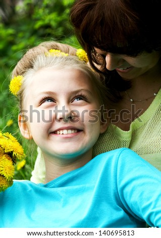 Smiling daughter looking at her mom in natural environment - stock photo