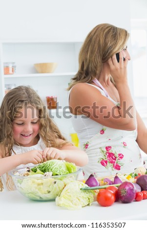 Smiling daughter preparing vegetable salad while her mother phoning by mobile phone - stock photo
