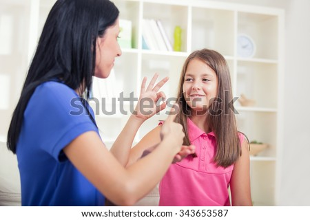 Smiling deaf girl learning sign language - stock photo
