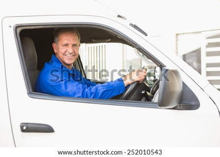 Smiling delivery man driving his van outside the warehouse - stock photo