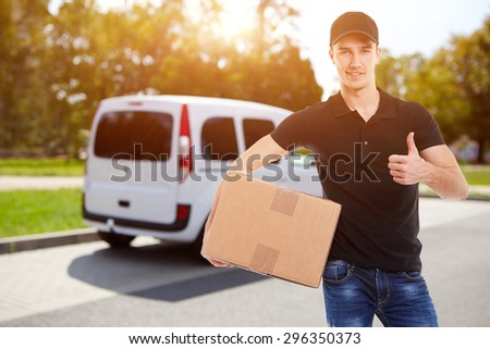 Smiling delivery man holding a cardboard box in sunlight - stock photo