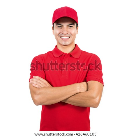 Smiling delivery man in red uniform standing with arm crossed - isolated on white background - stock photo