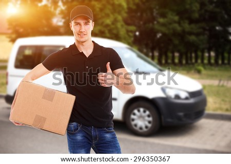 Smiling delivery man with a paper box in sunlight - stock photo