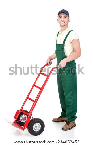 Smiling delivery man with hand truck, isolated on white background. - stock photo