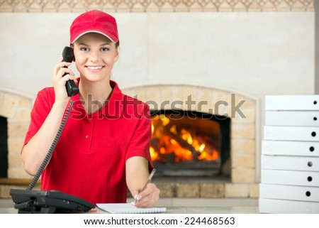 Smiling delivery woman of pizza holding pen and diary for placing order by phone. - stock photo