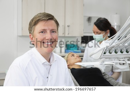 Smiling Dentist in front of patient and nurse - stock photo