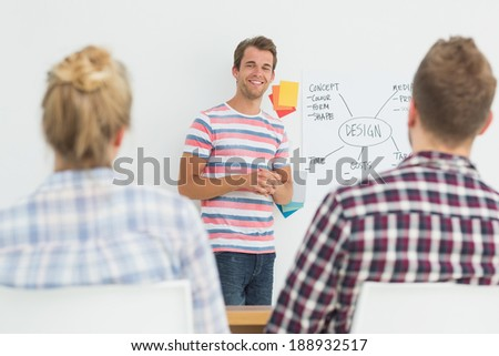 Smiling designer presenting ideas to colleagues in creative office - stock photo
