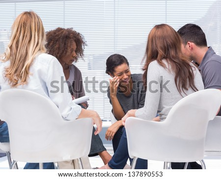 Smiling designer using his tablet pc while team works behind - stock photo