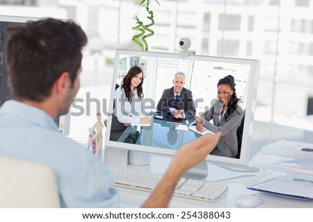 Smiling director sitting at the desk in front of the window between two employees against designer having a video chat - stock photo