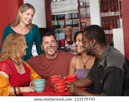 Smiling diverse group of mature adults in cafe - stock photo