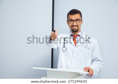 smiling doctor addressing audience at the presentation - stock photo