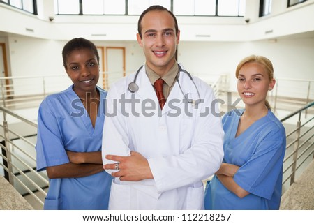 Smiling doctor and nurses looking at camera in hospital corridor - stock photo