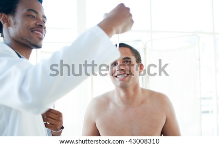 Smiling doctor checking male patient's temperature in a hospital - stock photo
