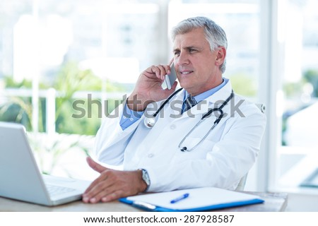 Smiling doctor having phone call at his desk in medical office - stock photo