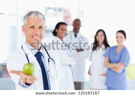 Smiling doctor holding an apple while his team is looking at him - stock photo