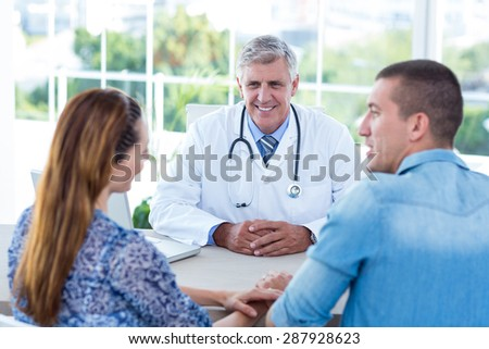 Smiling doctor looking at happy couple in medical office - stock photo