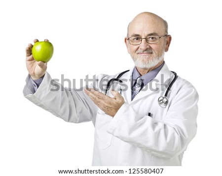 Smiling doctor presenting a green apple on his hand isolated in a white background - stock photo