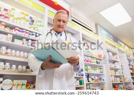 Smiling doctor reading a prescription in the pharmacy - stock photo