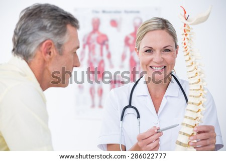 Smiling doctor showing her patient a spine model in medical office - stock photo