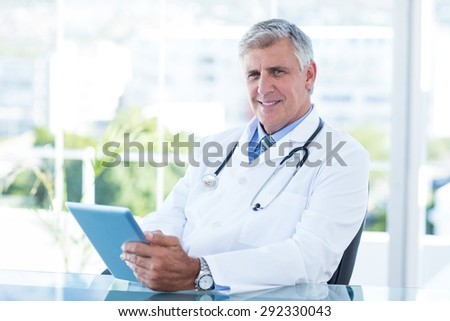 Smiling doctor sitting at his desk and holding tablet in medical office - stock photo