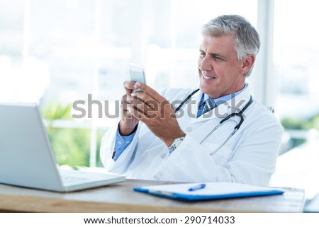 Smiling doctor sitting at his desk and texting in medical office - stock photo