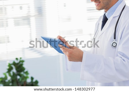 Smiling doctor using his tablet pc in medical office - stock photo